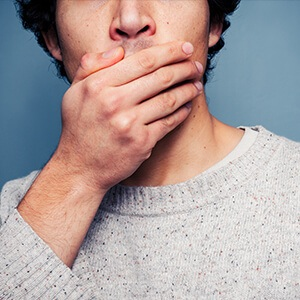 Closeup of man covering his mouth