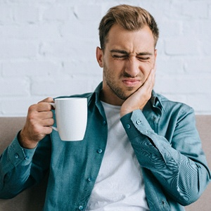 Man with tooth pain after drinking from coffee mug