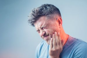 Older man in blue shirt with tooth pain